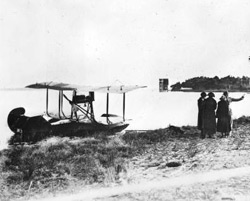 historic photo of old sea plane on the ocean shore.